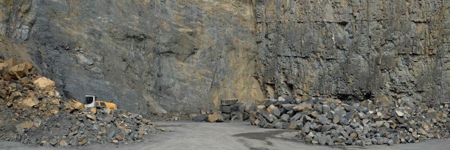Felswand des Steinbruchs in Ruggell mit Haufen von formwilden Steinen
